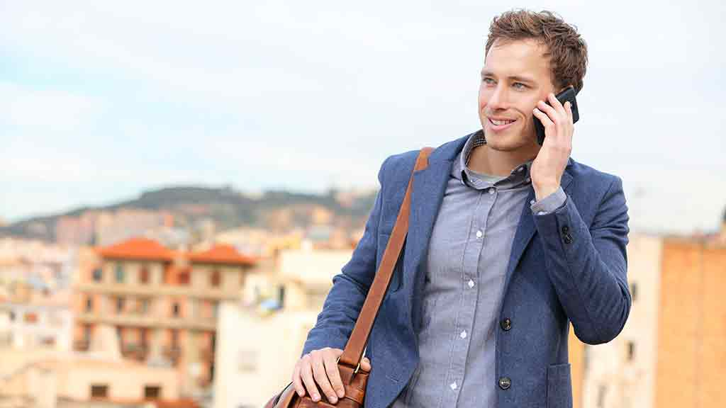 Small_Man talks on phone while traveling abroad