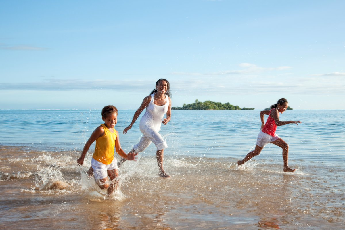 Single Parent playing with children on beach