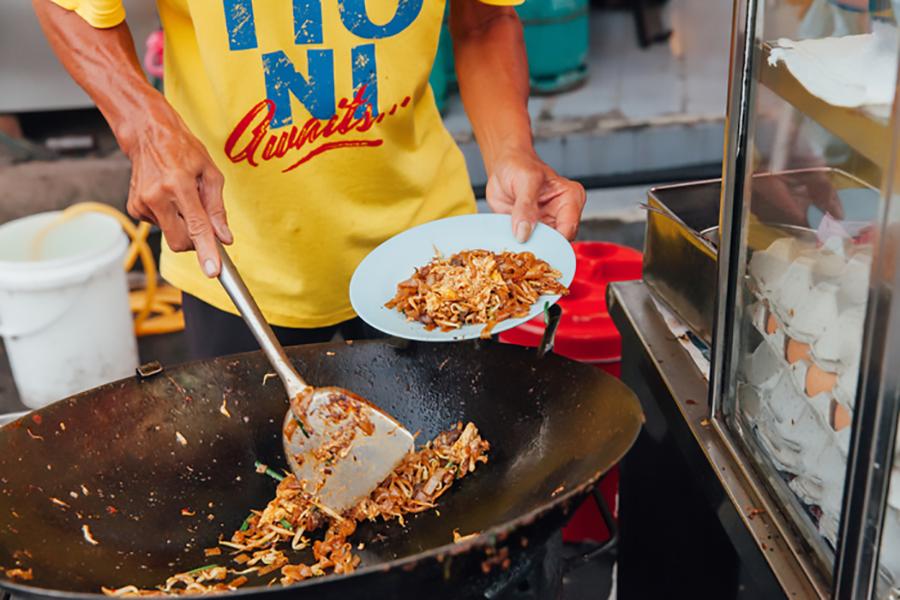 Man cooks Malaysian food in street market