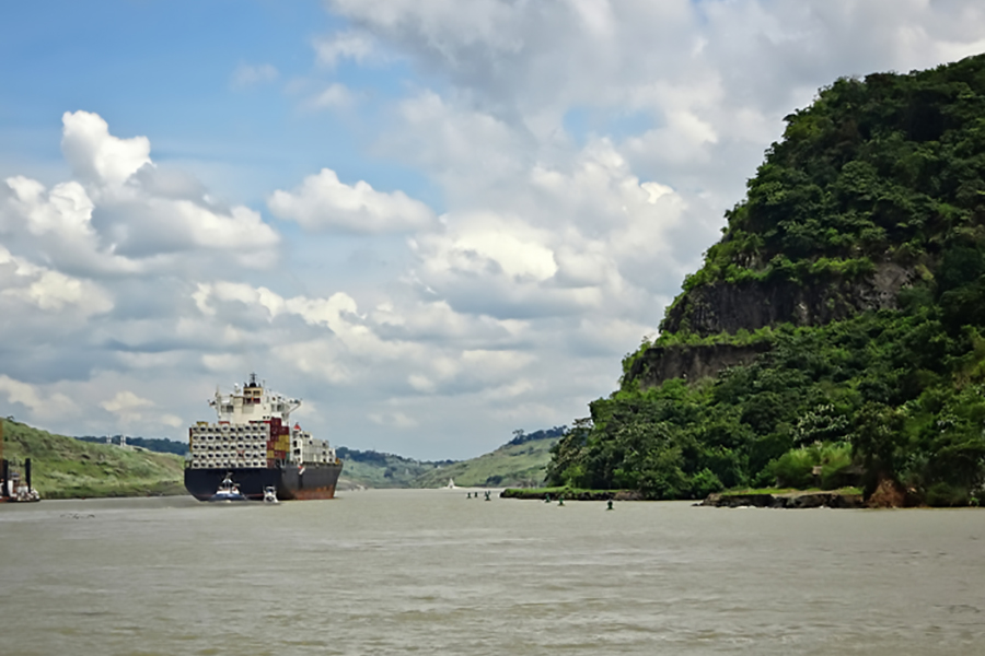 A cargo ship navigates the Panama Canal, flanked by the rainforest